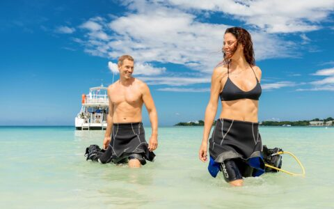 ouple with wetsuits half on walking in the water from a boat towards the shore