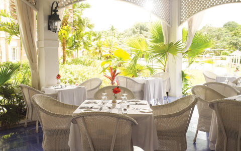 wicker dining chairs and white table cloth tables on a covered outdoor patio