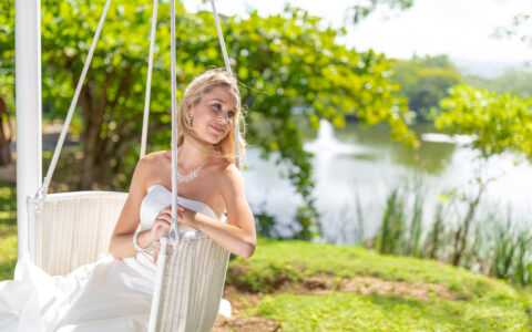 bride sitting in a white wicker swing looking off to the side