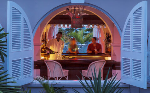 view of a bar area at night from a window with two white shutters open