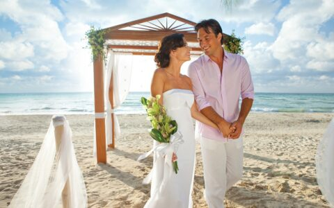 bride and groom in casual clothing at their beach wedding ceremony