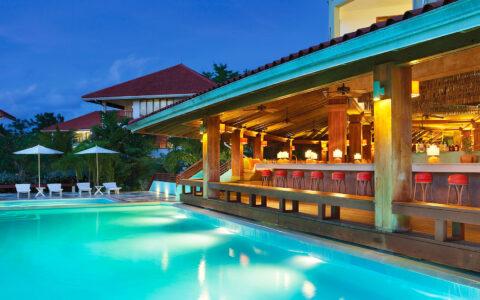 bar next to a pool illuminated at night