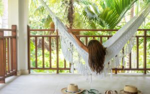 behind view of a woman laying on a hammock on a private balcony