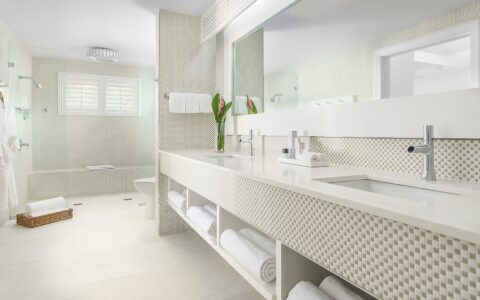 white bathroom decor with a glass shower, toilet, and vanity with two sinks