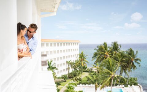 couple standing on a balcony overlooking the property and ocean