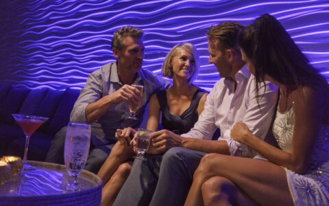 two couples sitting at a bar lounge area having drinks