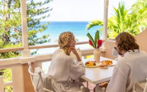 A couples enjoying breakfast overlooking the sea in Couples Resorts Jamaica