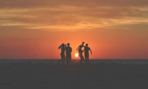 people dancing on a beach at sunset